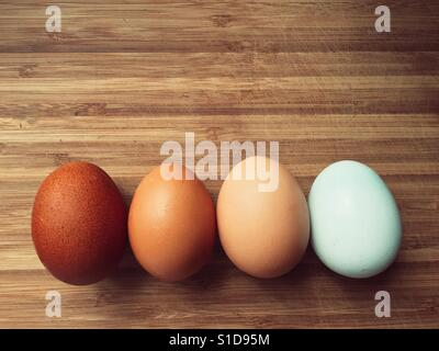 Four eggs in different shades on a wooden surface - Stock Photo