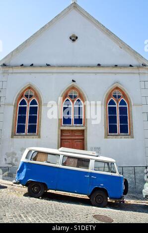 A vintage Volkswagen camper van parked in a sloping street in Lisbon, Portugal - Stock Photo