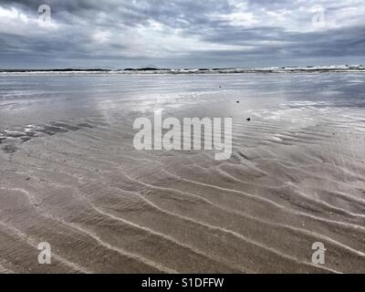 Ridges in sand and glow of light in the shallows of the sea in Cymyran beach, Rhosneigr, Anglesey, North Wales, - Stock Photo