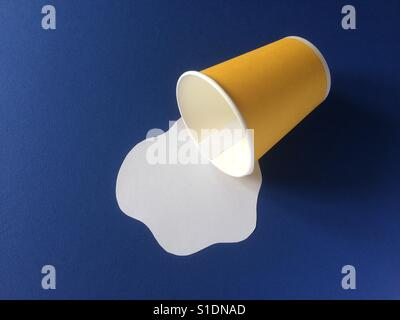 Milk spilled from yellow disposable cup on blue background. Paper craft concept. - Stock Photo