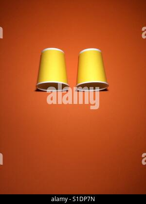 Two yellow disposable cups on orange textured paper background with copy space. - Stock Photo