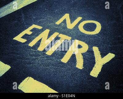 NO ENTRY. Words painted on a road instructing motorists, cyclists, buses and travellers they are not permitted to - Stock Photo