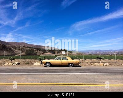 Yellow car parked along side road with farm land in backdrop. Location Ventura, CA - Stock Photo
