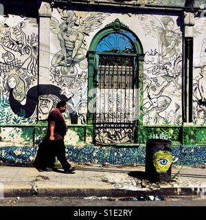 A Salvadoran man walks in front of a ruined house with Spanish colonial architecture elements, painted over by a - Stock Photo