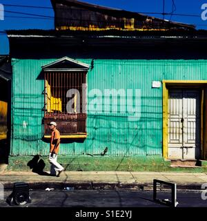 A Salvadoran man walks in front of a common lower middle class house, designed by using bold Spanish colonial architecture - Stock Photo
