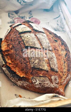 A loaf of sourdough bread with a crisp crust displayed in a rustic bread basket. Artisanal baking. - Stock Photo