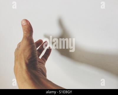 Male hand casting a shadow on the wall. Positive or hope concept. - Stock Photo