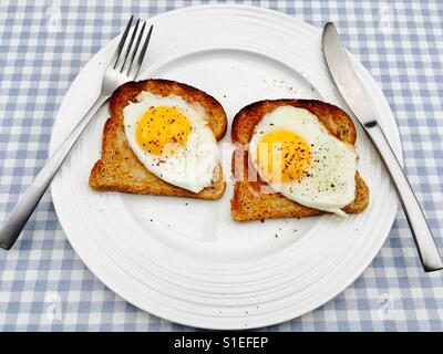 Fried eggs on toast with cracked black pepper - Stock Photo