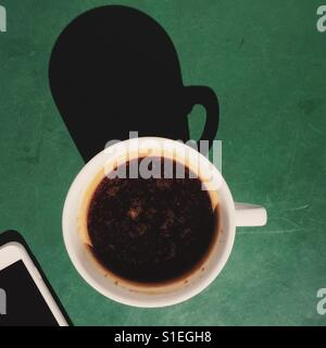 An overhead shot of a fresh Americano coffee beverage on a green table with a smart phone. - Stock Photo