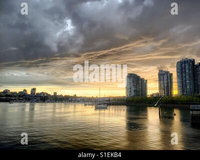 Sunset in Vancouver at False Creek. On the right site there a three high riser. In front the water, clouds are grey - Stock Photo