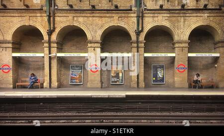 Two strangers waiting for a train at Notting Hill Gate tube station. - Stock Photo