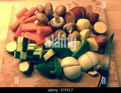 Chopped vegetables on  on a wooden cutting board. - Stock Photo