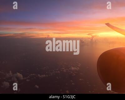 A view of the sunset over the ocean from a window of a plane - Stock Photo