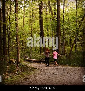 Two teenage friends walking in the park sharing secrets. - Stock Photo