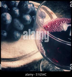 A glass of red wine with some 'Autumn Royal' table [eating] grapes on a wooden board. - Stock Photo