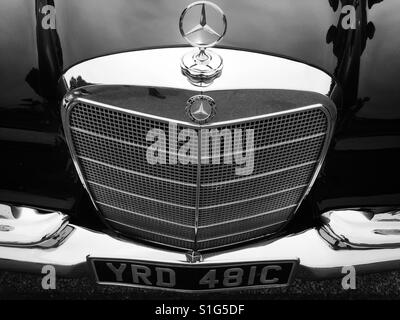 The radiator grill of a classic Mercedes car on display at a classic car show in Hartley Wintney in Hampshire. - Stock Photo