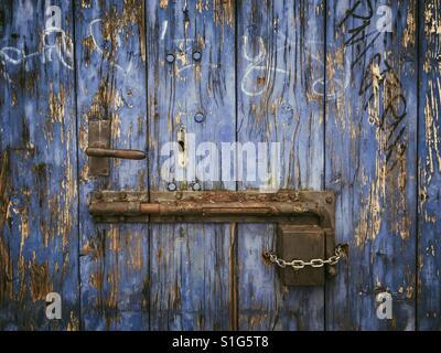 Rusty sliding door lock on weathered wooden blue door - Stock Photo