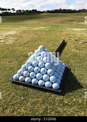 Pyramid of practice golf balls on driving range - Stock Photo