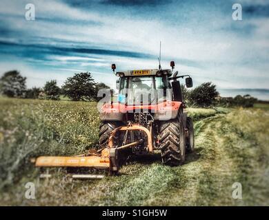 Farmer keeping a public footpath clear, Alderton, Suffolk, England. - Stock Photo