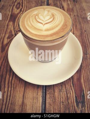 Flat white coffee in a glass cup in a wooden table - Stock Photo