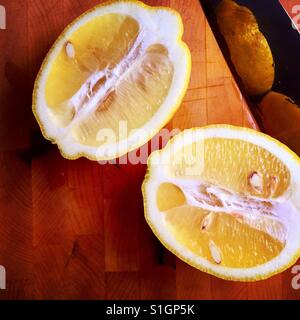 A fresh lemon cut in half on a wood cutting board with a knife - Stock Photo
