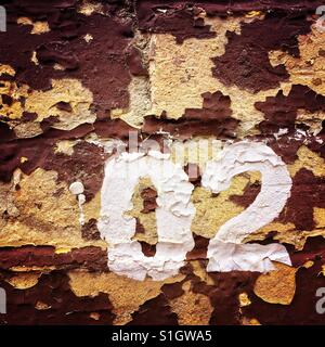 The numbers zero and two painted on a dilapidated brick wall - Stock Photo