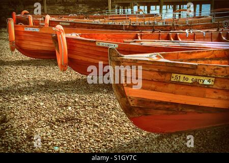 Wooden boats lined up along edge of lake - Stock Photo