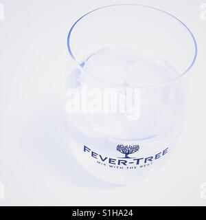 Gin and tonic in a Fever-Tree tonic glass, on a white background. - Stock Photo