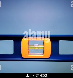 A close-up shot of a carpenter's level against a blue background - Stock Photo