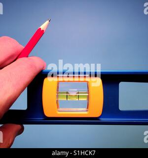A close up shot of a man holding a carpenter's level and a red pencil against a blue background - Stock Photo