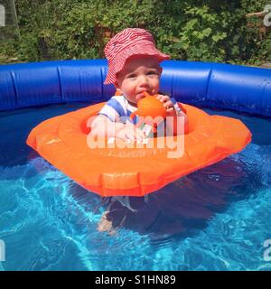Ten month old baby boy in a paddling pool - Stock Photo