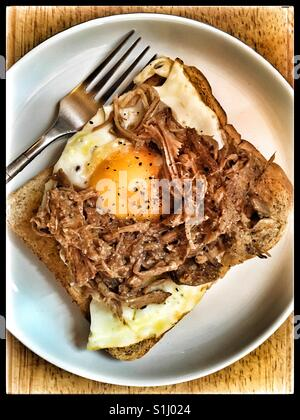 Pulled Pork and fried egg on buttered toast. - Stock Photo