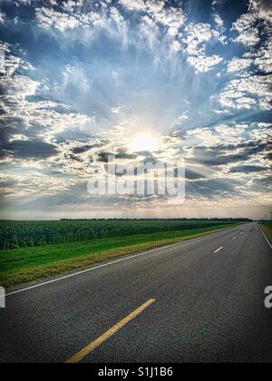 Awesome photo of sun rays bursting through clouds on a Kansas deserted road next to a corn field. - Stock Photo