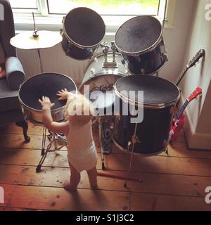 Ten month old baby boy playing the drums - Stock Photo