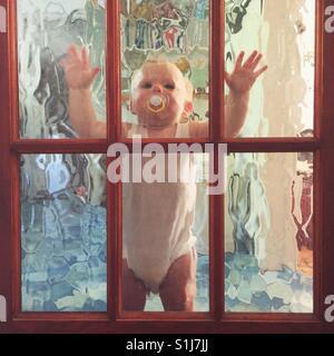 Ten month old baby boy standing against a glass internal door. - Stock Photo