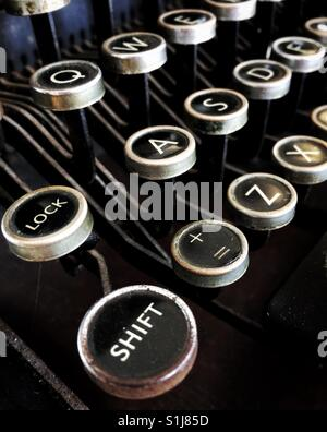 The shift key and other keys on the qwerty keyboard of an old-fashioned, Imperial, black and white typewriter. - Stock Photo