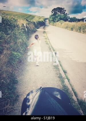 Cute little girl walking to school along a narrow rural Cornish road on a lovely warm sunny morning. Personal perspective - Stock Photo