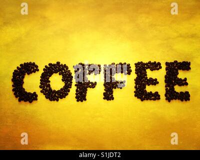 Coffee beans spelling out coffee on a yellow background - Stock Photo