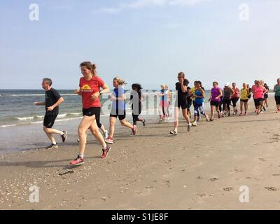 Kijkduin The Hague, the Netherlands - 8 July 2017: running club going for early morning run on the beach - Stock Photo