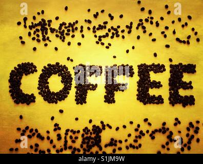 Coffee beans spelling out the word coffee on a yellow background - Stock Photo