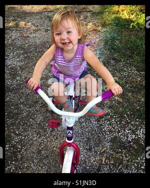 Happy little girl climbs up on her sisters bike that's way too big for her. - Stock Photo