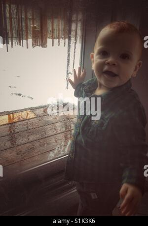 Baby boy looking out the window with snowy day outside. - Stock Photo