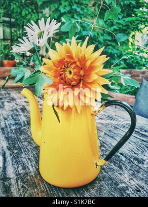 Yellow vase and flowers on a wooden table in Epirus, Greece - Stock Photo