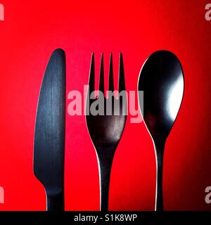 A close up overhead shot of a knife and a fork and a spoon above a red background - Stock Photo