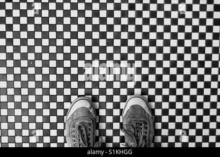 Looking down from above onto a pair of shoes in a shoe selfie standing on a black and white chequered floor - Stock Photo
