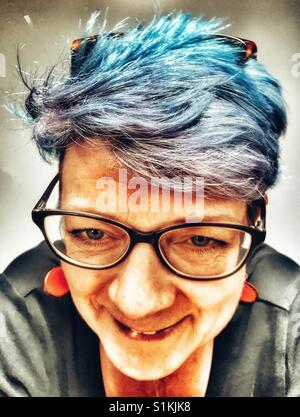 Woman with grey hair and dyed blue lowlights - Stock Photo