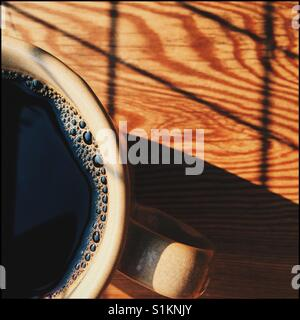 An overhead close-up shot of a fresh cup of black coffee on a wooden table with an interesting shadow pattern - Stock Photo