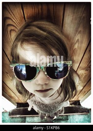 5 year old red haired girl in adult sunglasses. - Stock Photo