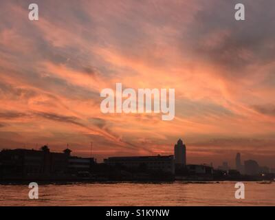 Sunrise on the Chao Phraya river as seen from Wat Arun in Bangkok, Thailand. - Stock Photo