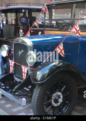 Antique Austin car at Costermongers annual festival decorated with bunting of British flag in London - Stock Photo